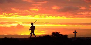 Silhouette of soldier against sunset and gravestone cross