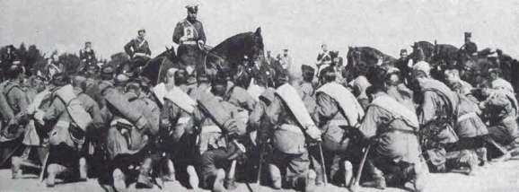 Czar Nicholas II at the Front holding an icon to bless his kneeling troops.