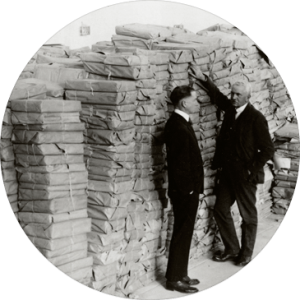 Professor Adams standing beside massive packages of documents removed by Hoover and transported to the west coast of America.